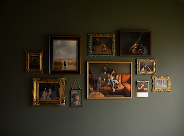 Gallery wall on dark olive green wall filled with family photos in gold and brass frames and an Artifact Uprising Gallery Frame in Walnut