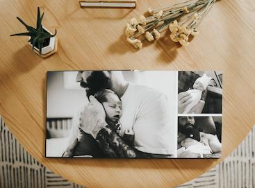 Artifact Uprising Layflat Photo Album on coffee table opened to photos of newborn baby