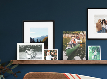 Artifact Uprising Metal Wooden Photo Ledge hung on royal blue wall and adorned with prints, frames, and photo books