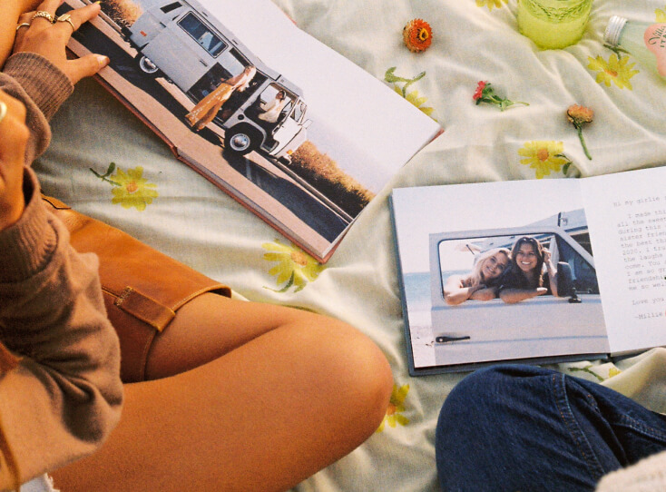 Two friends flipping through identical Artifact Uprising Everyday Photo Books featuring photos of a trip together